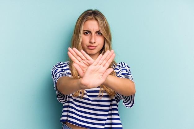 青の背景に孤立した若い白人のブロンドの女性は、一時停止の標識を示している手を伸ばして立って、あなたを妨げています。