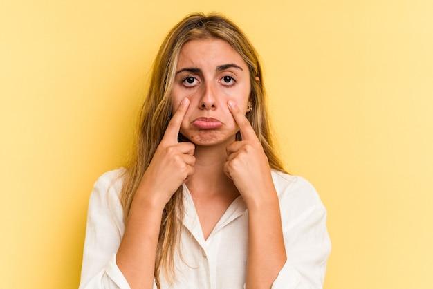 Молодая кавказская белокурая женщина изолирована на желтом фоне плачет, недовольна чем-то, агонией и концепцией замешательства.