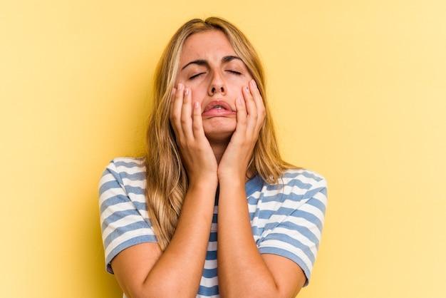 若い白人のブロンドの女性は、黄色の背景で泣いて、何かに不満、苦痛と混乱の概念に分離されました。