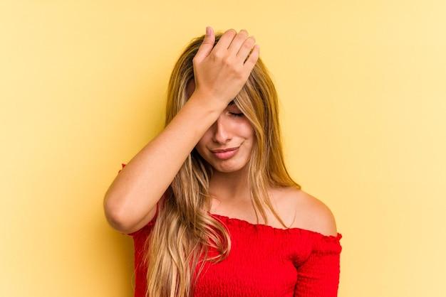 Молодая кавказская белокурая женщина изолирована на желтом фоне, забывая что-то, хлопая по лбу ладонью и закрывая глаза.