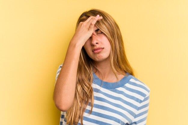 顔の正面に触れて、頭痛を持っている黄色の背景に分離された若い白人のブロンドの女性。