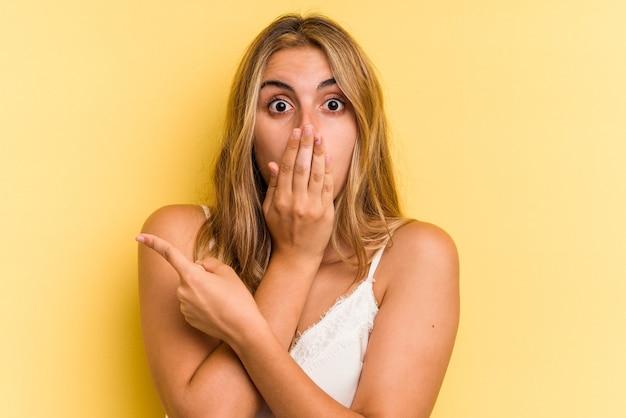 側面を指している黄色の背景に分離された若い白人金髪女性