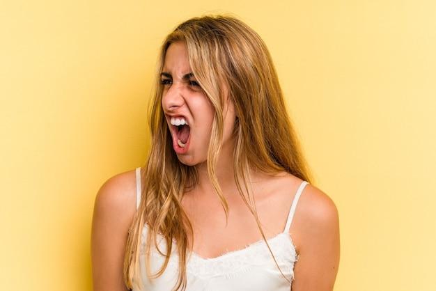 非常に怒っている、怒りの概念、欲求不満を叫んで黄色の背景に分離された若い白人のブロンドの女性。