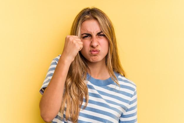 카메라에 주먹을 보여주는 노란색 배경에 고립 된 젊은 백인 금발 여자, 공격적인 표정.