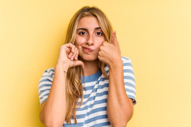 親指を上と親指を下に示す黄色の背景に分離された若い白人のブロンドの女性、難しい選択の概念