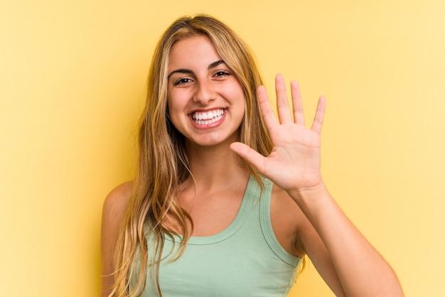黄色の背景に分離された若い白人のブロンドの女性は、指で5番を示して陽気に笑っています。