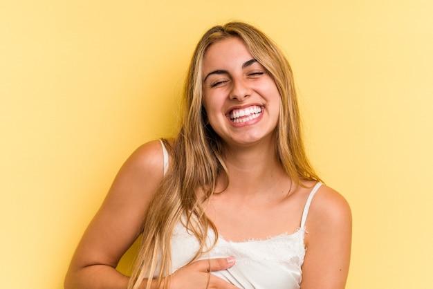 黄色の背景に分離された若い白人のブロンドの女性は、おなかに触れ、優しく微笑んで、食事と満足の概念。