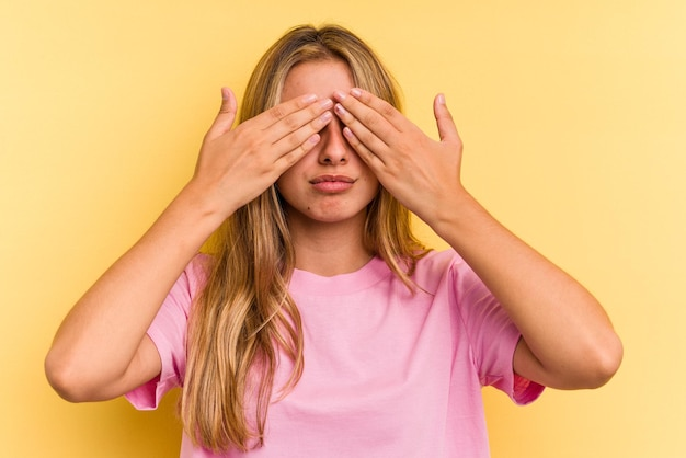 Young caucasian blonde woman isolated on yellow background  afraid covering eyes with hands.