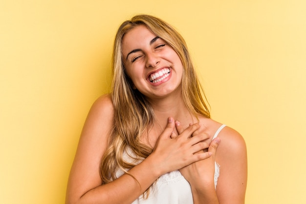 Young caucasian blonde woman isolated on yellow background  has friendly expression, pressing palm to chest. love concept.