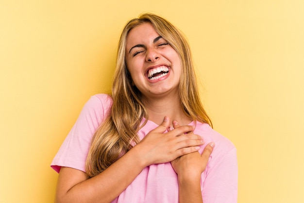 Young caucasian blonde woman isolated on yellow background  laughing keeping hands on heart, concept of happiness.