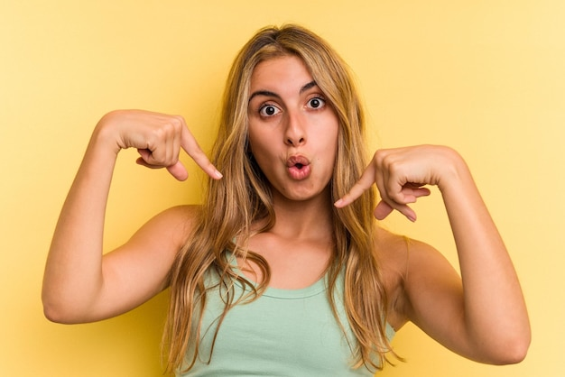 Young caucasian blonde woman isolated on yellow background  points down with fingers, positive feeling.