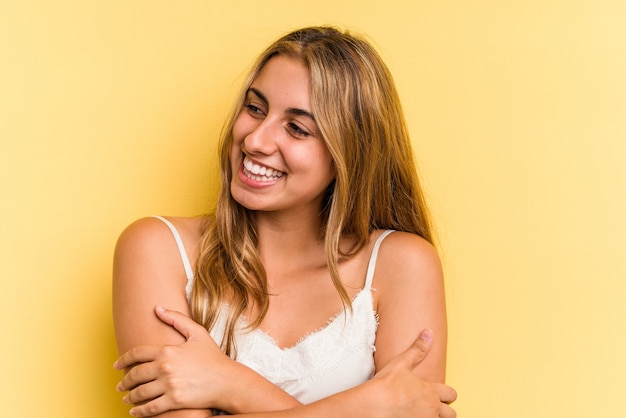 Young caucasian blonde woman isolated on yellow background  smiling confident with crossed arms.