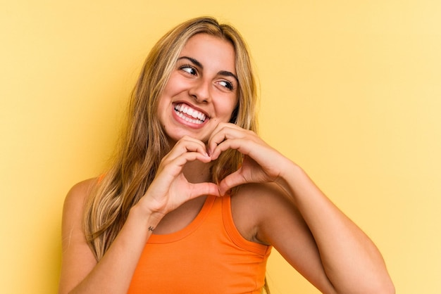 Young caucasian blonde woman isolated on yellow background  smiling and showing a heart shape with hands.