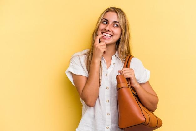黄色の背景に分離された革のバッグを身に着けている若い白人のブロンドの女性は、コピースペースを見ている何かについて考えてリラックスしました。