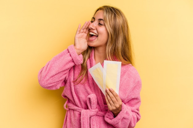 黄色の背景で隔離された除毛バンドを保持し、開いた口の近くで叫び、手のひらを保持しているバスローブを着ている若い白人のブロンドの女性。 Premium写真