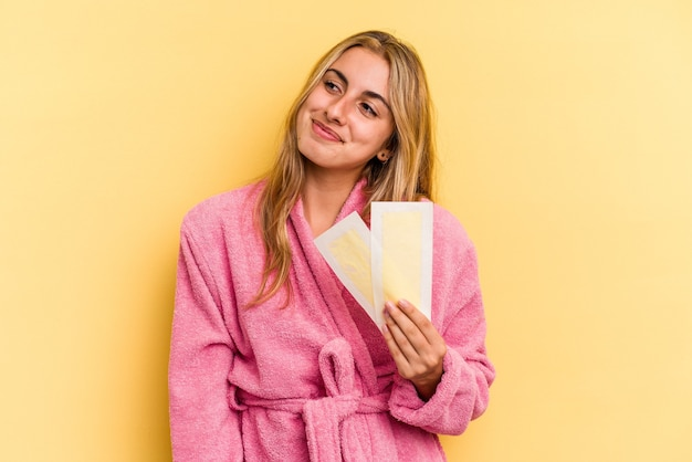 Young caucasian blonde woman wearing bathrobe holding depilatory bands isolated on yellow background  dreaming of achieving goals and purposes