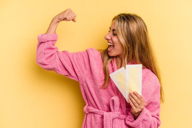 Young caucasian blonde woman wearing bathrobe holding depilatory bands isolated on yellow background  raising fist after a victory, winner concept.