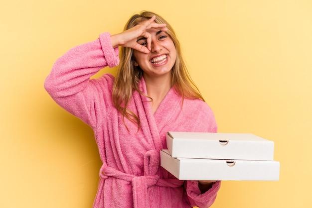 黄色の背景に分離されたピザを保持しているバスローブを着ている若い白人のブロンドの女性は、目に大丈夫なジェスチャーを維持して興奮しています。
