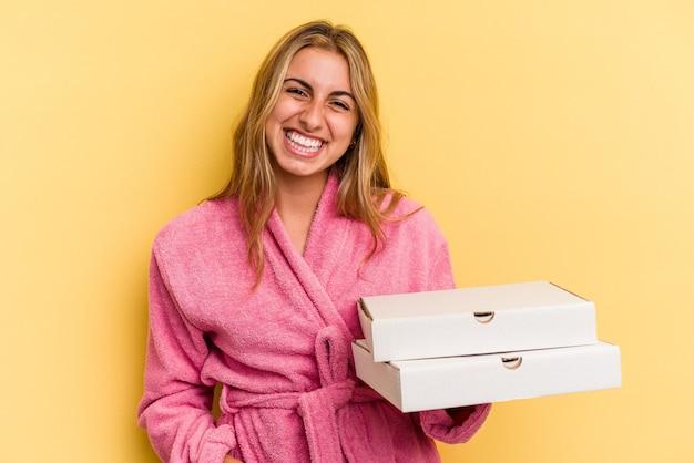 黄色の背景で隔離のピザを保持しているバスローブを着ている若い白人のブロンドの女性は幸せ、笑顔、陽気な。