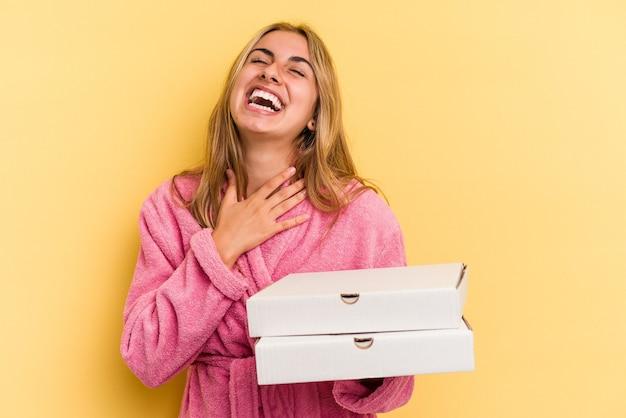 黄色の背景で隔離のピザを保持しているバスローブを着ている若い白人のブロンドの女性は、胸に手を置いて大声で笑います。