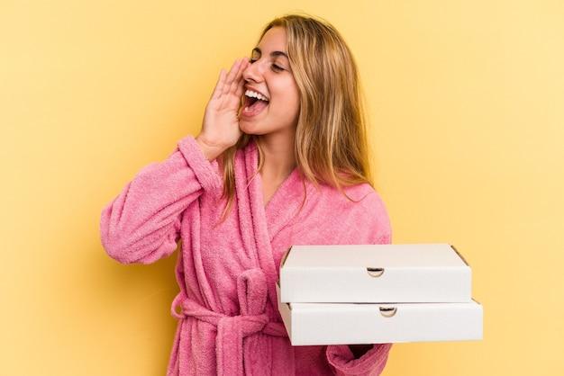 黄色の背景に分離されたピザを持って叫び、開いた口の近くで手のひらを保持しているバスローブを着ている若い白人のブロンドの女性。