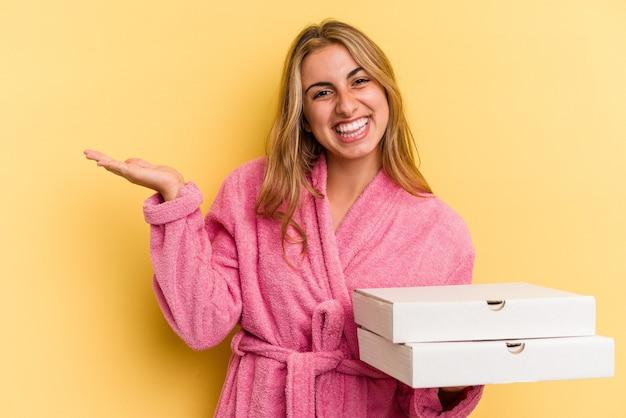 手のひらにコピースペースを示し、腰に別の手を保持している黄色の背景で隔離のピザを保持しているバスローブを着ている若い白人のブロンドの女性。