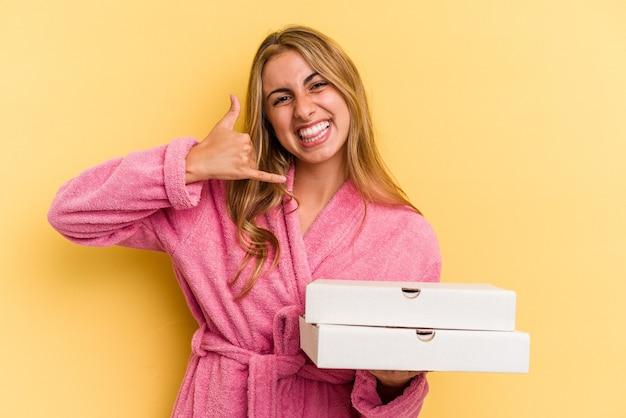 指で携帯電話の呼び出しジェスチャーを示す黄色の背景に分離されたピザを保持しているバスローブを着ている若い白人のブロンドの女性。