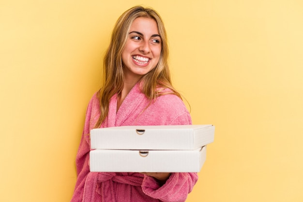 Young caucasian blonde woman wearing bathrobe holding pizzas isolated on yellow background  looks aside smiling, cheerful and pleasant.
