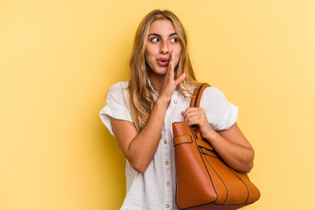 Young caucasian blonde woman wearing a leather bag isolated on yellow background  is saying a secret hot braking news and looking aside