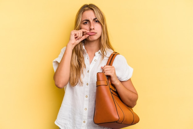 Young caucasian blonde woman wearing a leather bag isolated on yellow background  with fingers on lips keeping a secret.