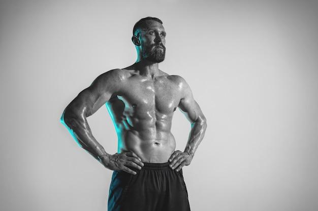 네온 불빛에 스튜디오 배경 위에 젊은 백인 보디 빌딩 훈련. 크로스 핏 운동 후 휴식하는 근육질 남성 모델. 스포츠, 보디 빌딩, 건강한 라이프 스타일, 동작 및 행동의 개념.