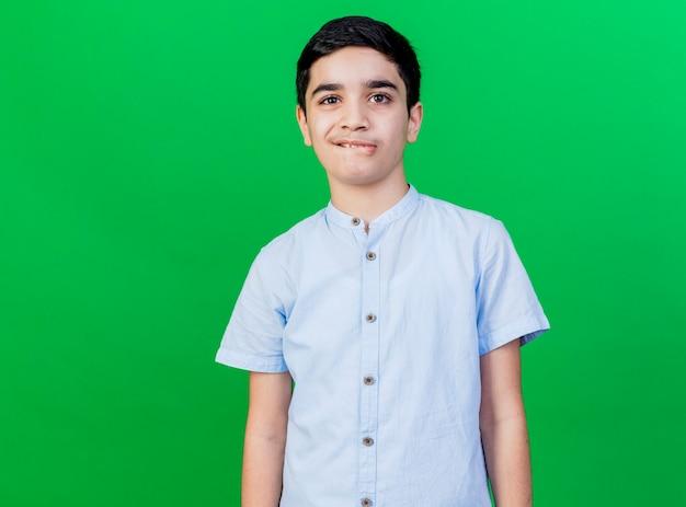 Labbro mordace del giovane ragazzo caucasico isolato sulla parete verde con lo spazio della copia