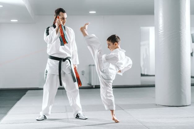 Young caucasian boy in dobok kicking barefoot while trainer holding kick target. taekwondo training concept.