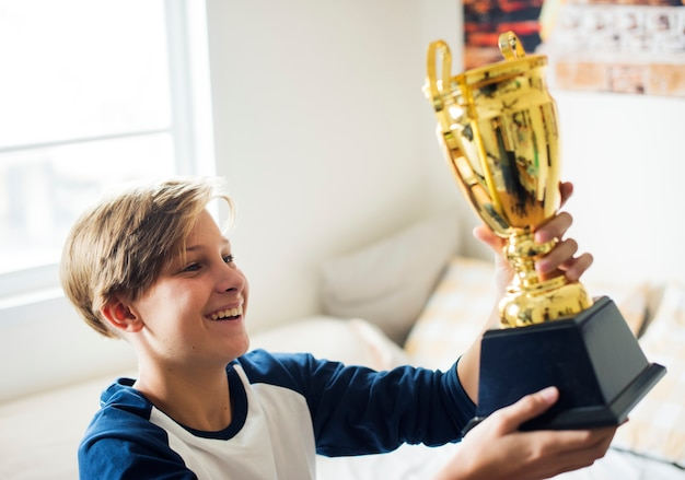Young caucasian boy holding trophy cheerful happiness