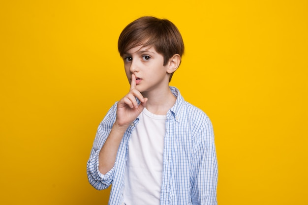 Young caucasian boy is gesturing the silence soung posing serious on a yellow studio wall in casual clothes