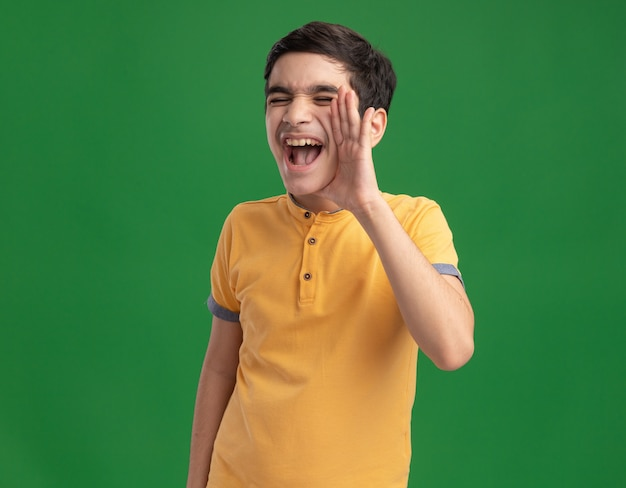 Young caucasian boy keeping hand near mouth calling out loud to someone with closed eyes isolated on green wall with copy space