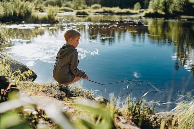 일몰에 긴 막대를 들고 연못에서 낚시를 하는 척 하는 젊은 백인 소년