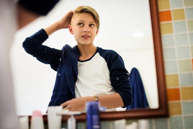Молодой кавказский мальчик установил волосы с зеркалом в ванной комнате