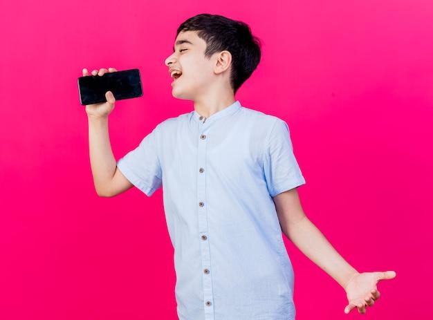 진홍색 배경에 고립 된 마이크로 휴대 전화를 사용하여 빈 손을 보여주는 젊은 백인 소년 노래