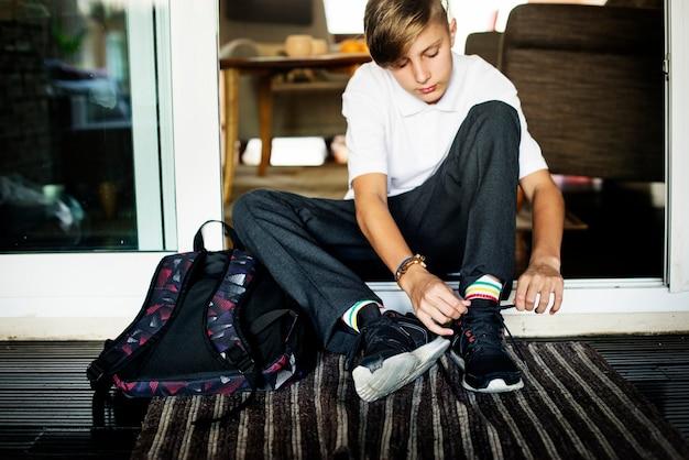 집 입구에 앉아 운동화 밧줄을 묶는 젊은 백인 소년