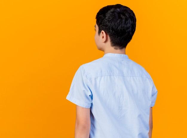 복사 공간 오렌지 배경에 고립 된보기 뒤에 서있는 어린 백인 소년