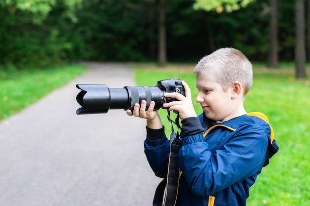 デジタル一眼レフカメラで撮影している白人の少年。自然環境。