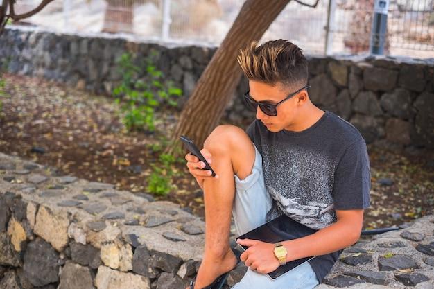 Молодой кавказский мальчик пользуется мобильным телефоном в саду, сидя и отдыхая - люди нового поколения онлайн, подключенные к интернету и общественной жизни