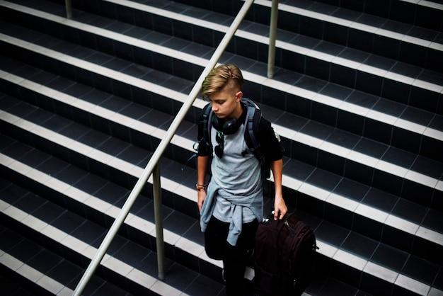 Молодой кавказский мальчик просыпаясь вниз по лестнице с багажом