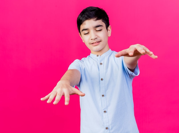진홍색 배경에 고립 된 카메라를 향해 손을 뻗어 닫힌 눈으로 걷는 어린 백인 소년