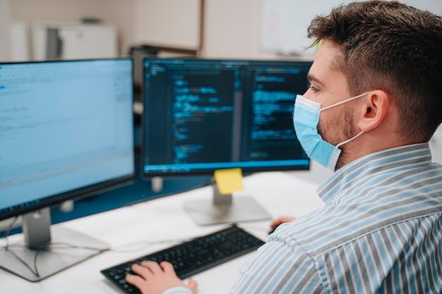 컴퓨터 과학자로 일하는 얼굴 마스크를 쓰고 어린 백인 소년