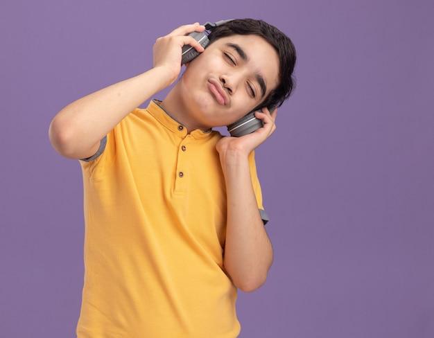 Giovane ragazzo caucasico che indossa e afferra le cuffie godendosi la musica con le labbra increspate e gli occhi chiusi isolati sulla parete viola con spazio di copia