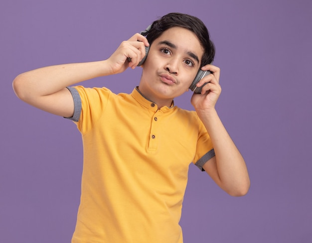 Young caucasian boy wearing and grabbing headphones looking straight listening to music with pursed lips isolated on purple wall