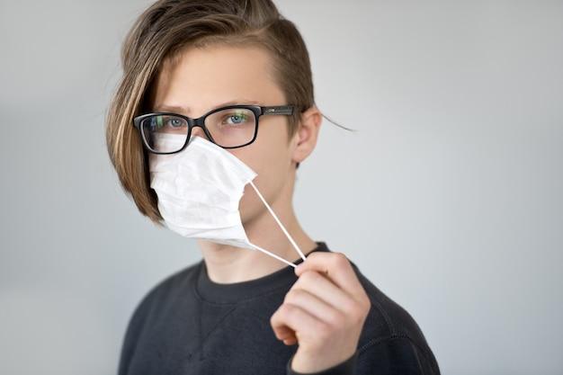 코로나 바이러스에 대한 보호 마스크를 착용하는 젊은 백인 소년. 바이러스로부터 예방하기 위해 외과 마스크를 착용하는 사람.