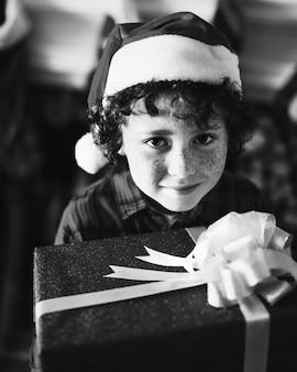 Giovane ragazzo caucasico con un regalo di natale